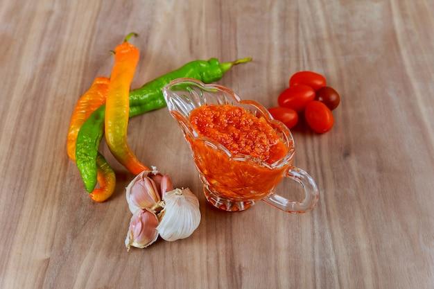 Сырой горячий грузинский соус аджика и ингредиенты на деревянном столе