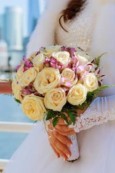 ピンクと白のバラのウェディングブーケを持って花嫁