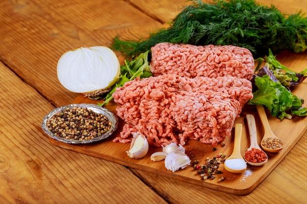 素朴な木製のテーブルの上の紙に新鮮な生のひき肉