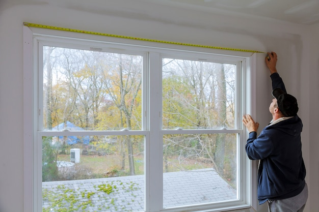 新しい家の窓の上で工事中の測定と釘打ちのプロセス