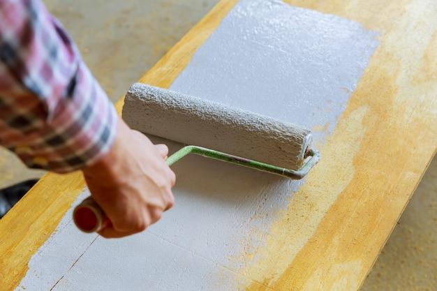 白いペンキローラーで木を塗る