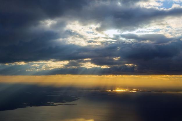 海の上を飛んでいる飛行機の翼を持つ朝の日の出。