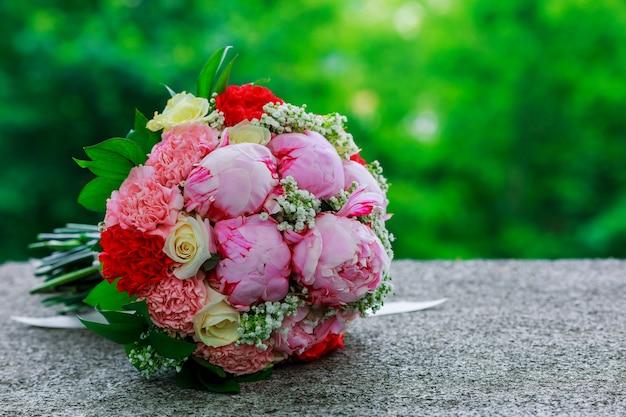 白い蘭の花、デイジーと赤い果実のウェディングブライダルブーケ
