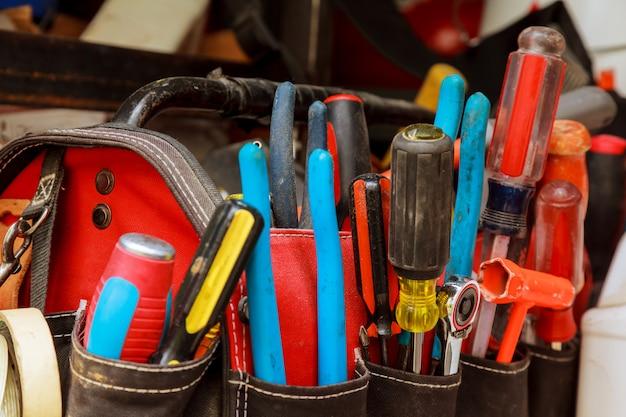 Инструменты работы в сумке на деревянной предпосылке.