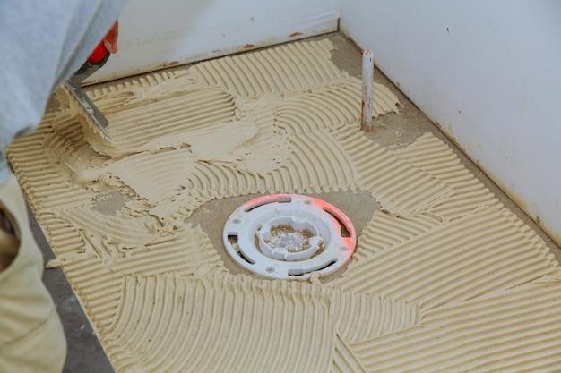 マスターはタイル張りのための床の接着剤を置きます