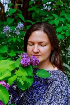 少女はライラックの素晴らしい香りを楽しんでいます。手に花が咲くライラックツリーの近くに立っています。
