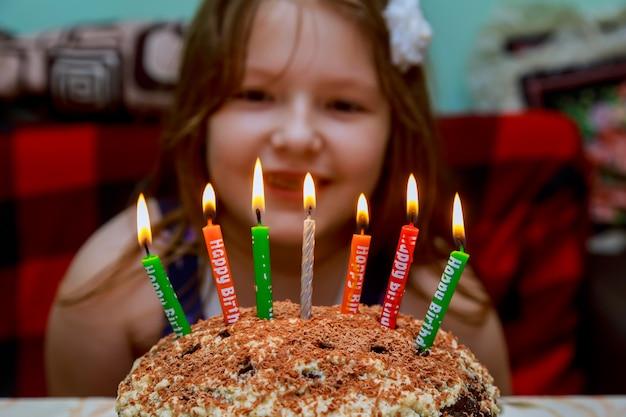 Маленькая девочка дует свечи торт ко дню рождения со свечами