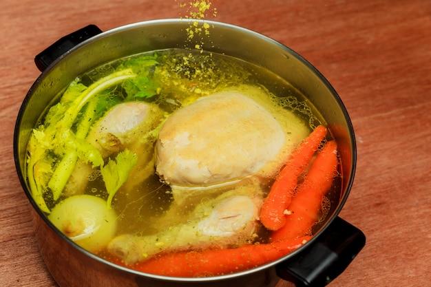 チキンスープニンジンチキングリーンクラッカーが入ったボウルにチキンスープ。