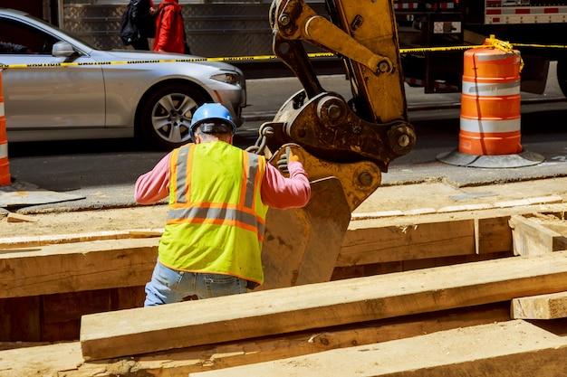 都市通信パイプラインの設置ショベルの修理は、交換用の古いパイプのための溝を掘りました。