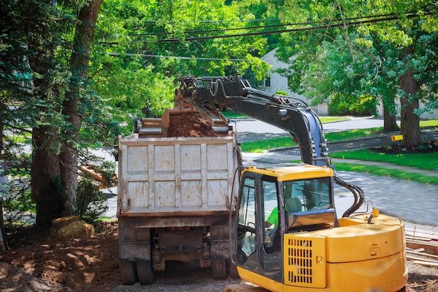 黄色い坑夫の大きい掘削機のバケツは土を集め、建築家で石切り場で石を注ぐ。