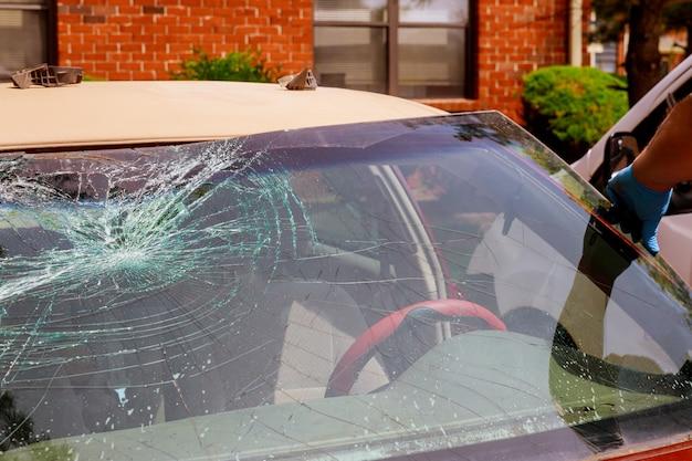 自動車の特別作業員が自動車のサービスステーションで壊れたフロントガラスや車のフロントガラスを取り除く