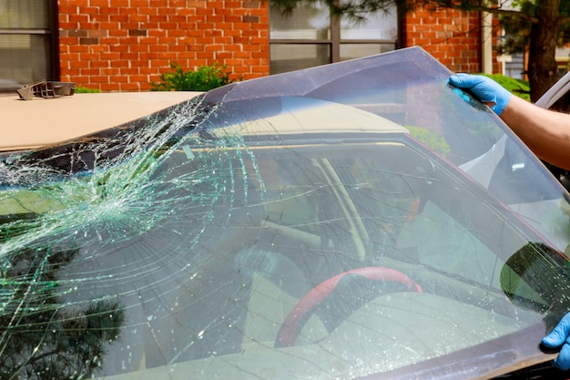 労働者は自動車サービスで車のクラッシュしたフロントガラスを取り除く