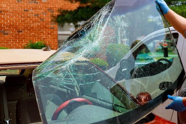 壊れたフロントガラス車の特別な労働者は自動車サービスで車のフロントガラスを取ります