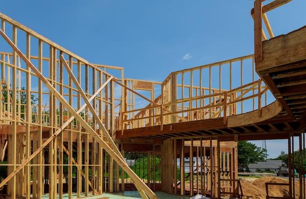 内側からの澄んだ空を背景に建設中の天然素材から新しい木のエコ住宅。