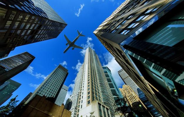 Глядя на небоскребы нью-йорка в финансовом районе, нью-йорк, сша летит самолет