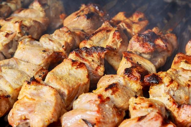 Сырье шашлык гриль на металлическом шампуре. запекание сырого мяса на гриле.