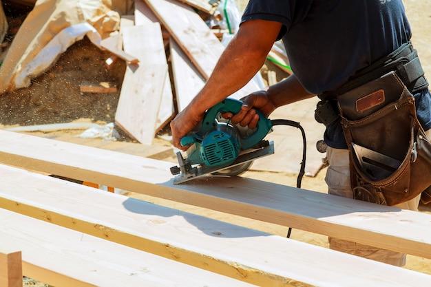 木の板を切断するための丸のこを使用して大工。男性労働者の建設の詳細