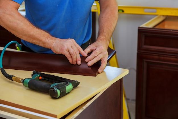 トリムをフレーミングするキッチンキャビネットのクラウンモールディングにネイルガンを使用して大工のブラッド