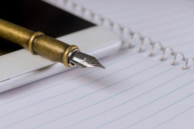 Смартфон, блокнот и ручка на сто долларовых купюр.