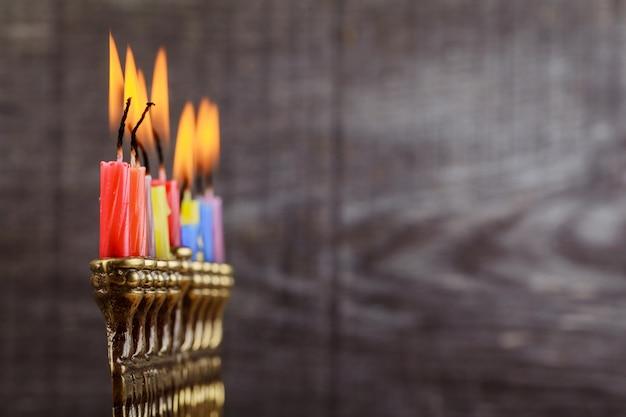 ユダヤ人の祝日のハヌカのシンボル - 本枝の燭台、ドーナツ、チョコレートコイン、木製のドレイドル。