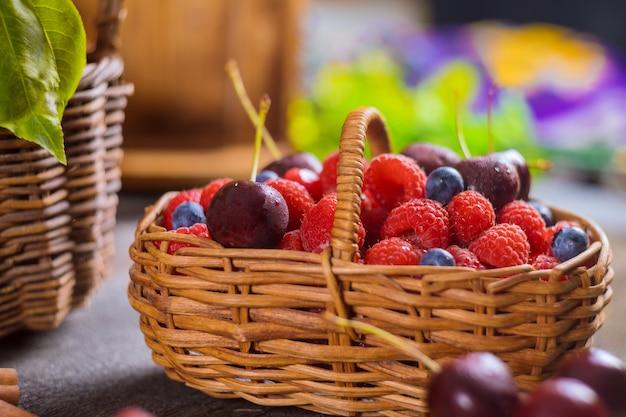 混合夏ベリーのバスケットブルーベリー、チェリー、ラズベリーの健康食品のセレクティブフォーカス。