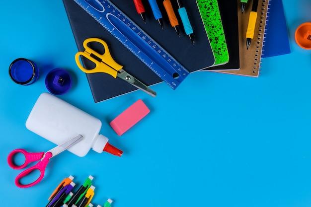 学校に戻って、明るい青の背景に学用品