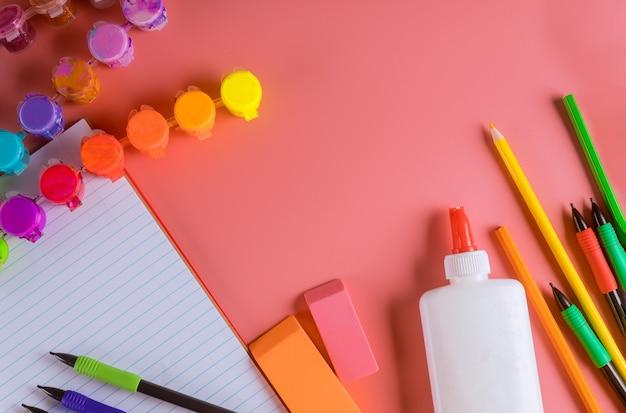 ピンクの背景の学校の付属品。塗料、鉛筆、接着剤