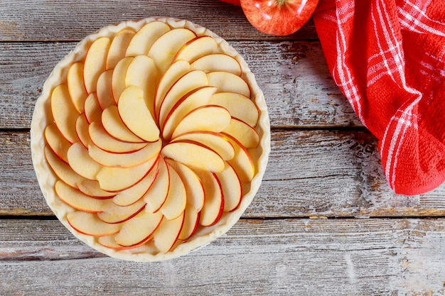 木製のテーブルに生のアップルパイ。焼く準備ができて