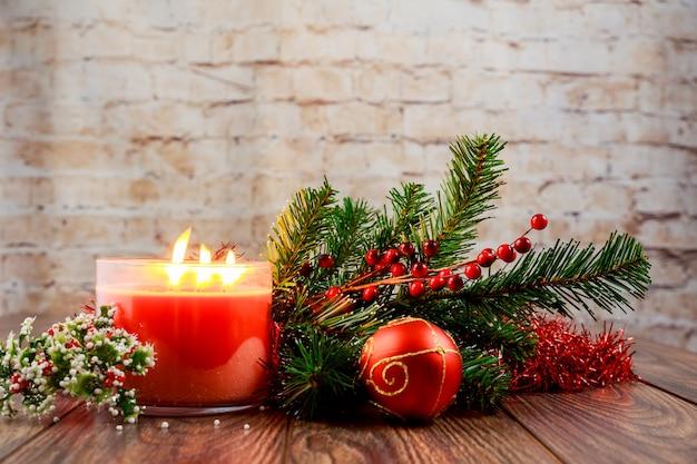 Свеча и украшения рождества на белом деревянном столе с космосом экземпляра.