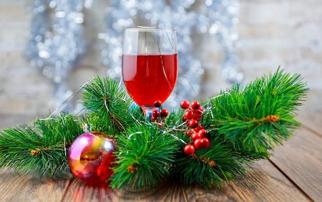 休日のクリスマスツリーの前で赤ワインのグラス