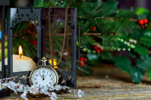 クリスマスツリーのモミの枝、真夜中の時計、ろうそく、ゴールデンボール、垂直の古い木製のデスクテーブルの背景にガーランドライトと新年のカード。