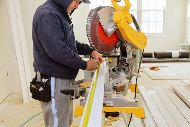 丸鋸切断クラウンモールディングを使用して改修する請負業者。