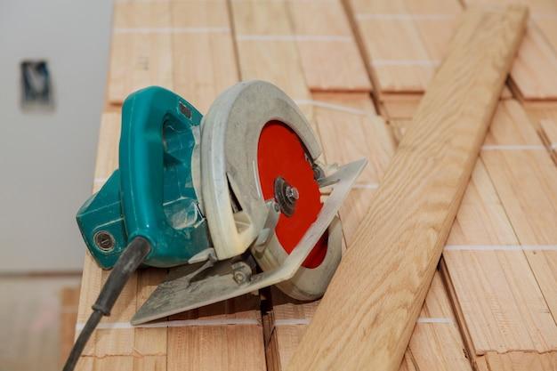 電気のこぎりで古い寄木細工の床を切る