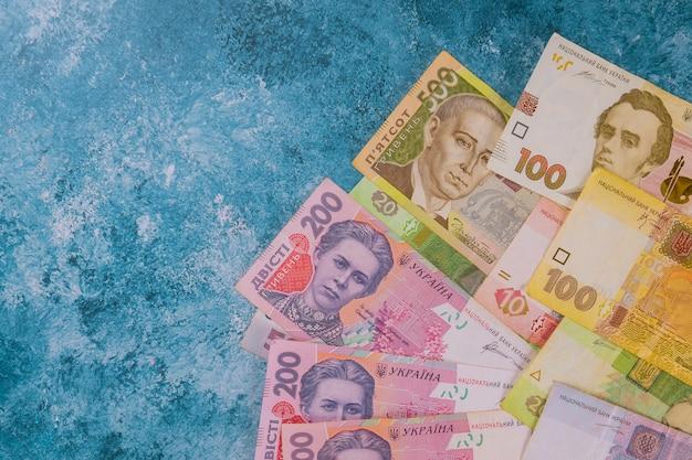青色の背景にウクライナのお金。ファイナンス。
