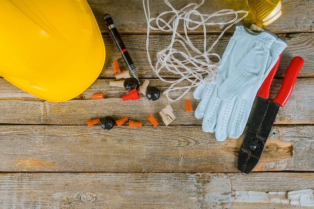 職場の電気技師は、電気工事と黄色いヘルメットで使用されるツールとケーブルを準備します