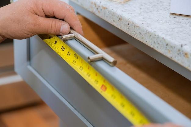 大工は台所で引き出しを測定する男を構築しています