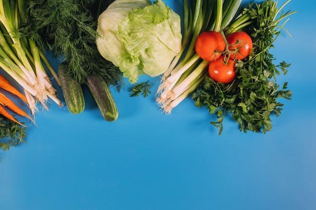 青いテーブルに新鮮な野菜。