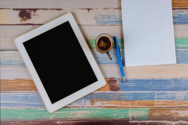 一杯のコーヒーとタブレットとノートとペン。