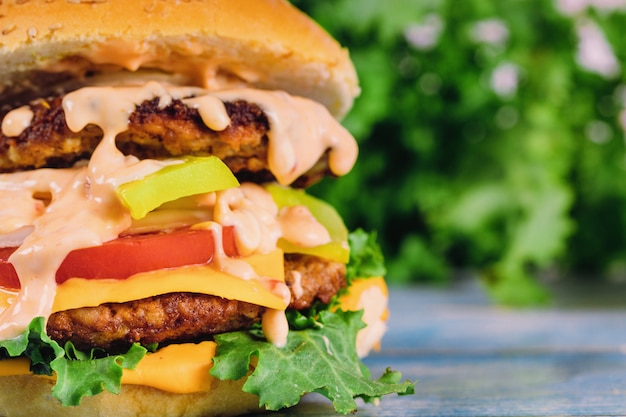 Домашний гамбургер с листьями салата, сыром, луком и помидорами.