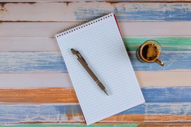 ノート、ペン、テーブルの上のコーヒーカップ。