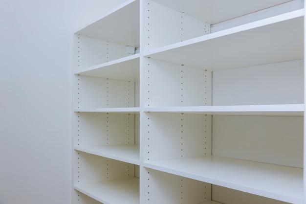 白いプラスチック製キャビネットの内部または多くの空の棚が取り付けられた衣服。