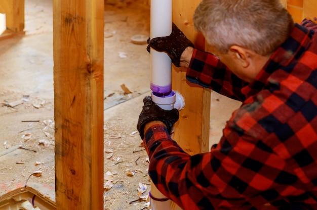 建設中の排水用の接着剤でプラスチックパイプを接合する配管工