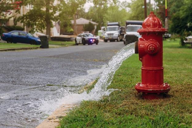Вода, вытекающая из открытого красного пожарного гидранта, мокрая от брызг.