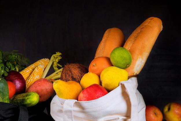 野菜と果物が入った布製の再利用可能なバッグ。