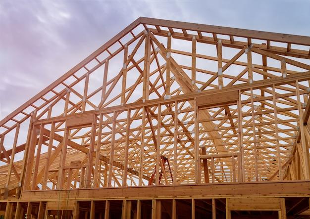 建物の建設、建設中の屋根の下で新しい家を組み立てる木材