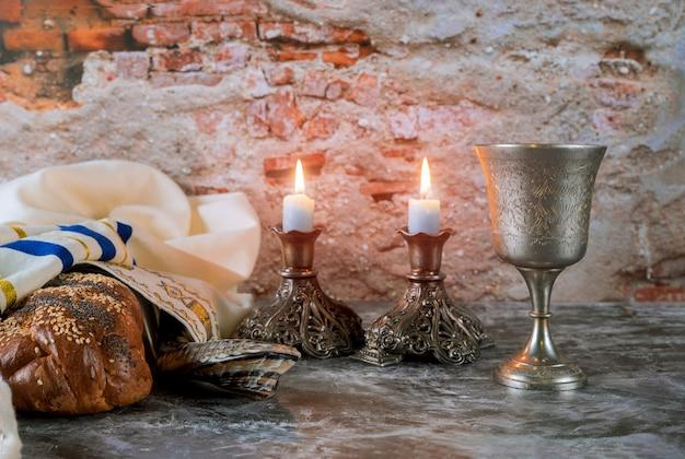安息日ユダヤ人の休日のカラパンと木製のテーブルの上のカンデラ