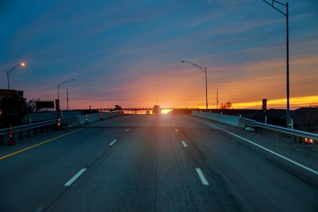 夜明けの夕日の光の中で曇り空と田舎道