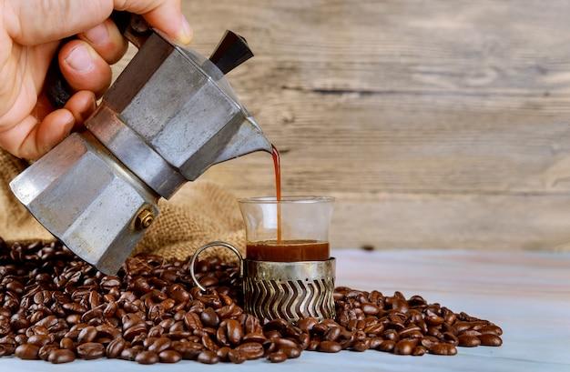 フレンチはコーヒー豆のエスプレッソコーヒーのガラスカップにコーヒーを注ぐ