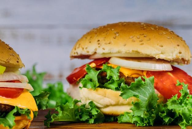 木製の背景に自家製のハンバーガー。閉じる。