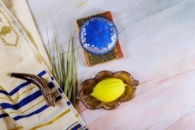Еврейский ритуал праздника суккот под еврейским религиозным символом этрог, лулав, хадас, арава талит молитвенная книга киппа и шофар